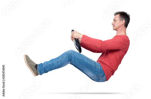Man in jeans and red t-shirt drives a car with a steering wheel, isolated on white background Fototapet