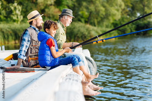Men of three generations fishing all together Canvas