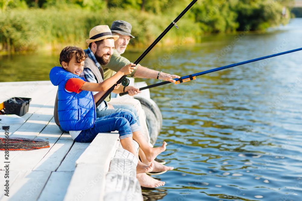 Fototapeta Men of three generations feeling happy while fishing in summer