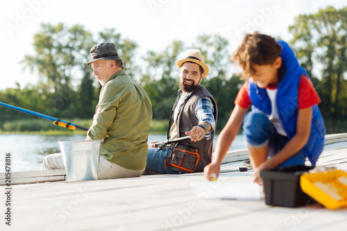 Fotografija  Bearded father asking his son to find fishing hook