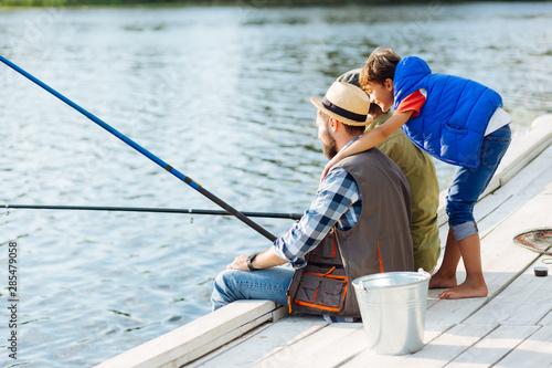 Foto auf AluDibond Fischerei Boy wearing blue vest hugging his father and grandfather