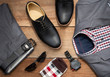Leinwandbild Motiv Men fashion casual clothing set and accessories isolated on wooden background include black derby shoes, gray suit, pants, belt, sunglass, sock and scottis office shirt. Flat lay, top view