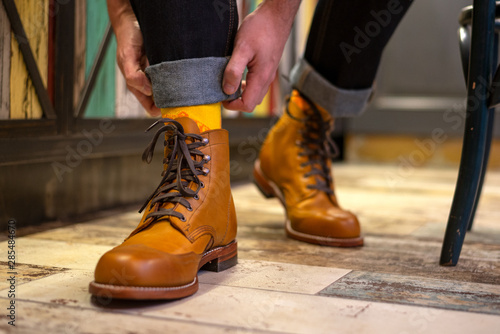 Obraz na plátně  Man ordering his jeans and wearing yelloe brown brogues boots indoor, close up v