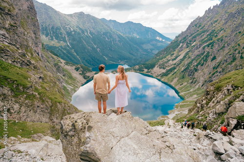 Happy loving couple standing together at stone in High Tatra national park in Poland with a picturesque landscape on background Canvas Print