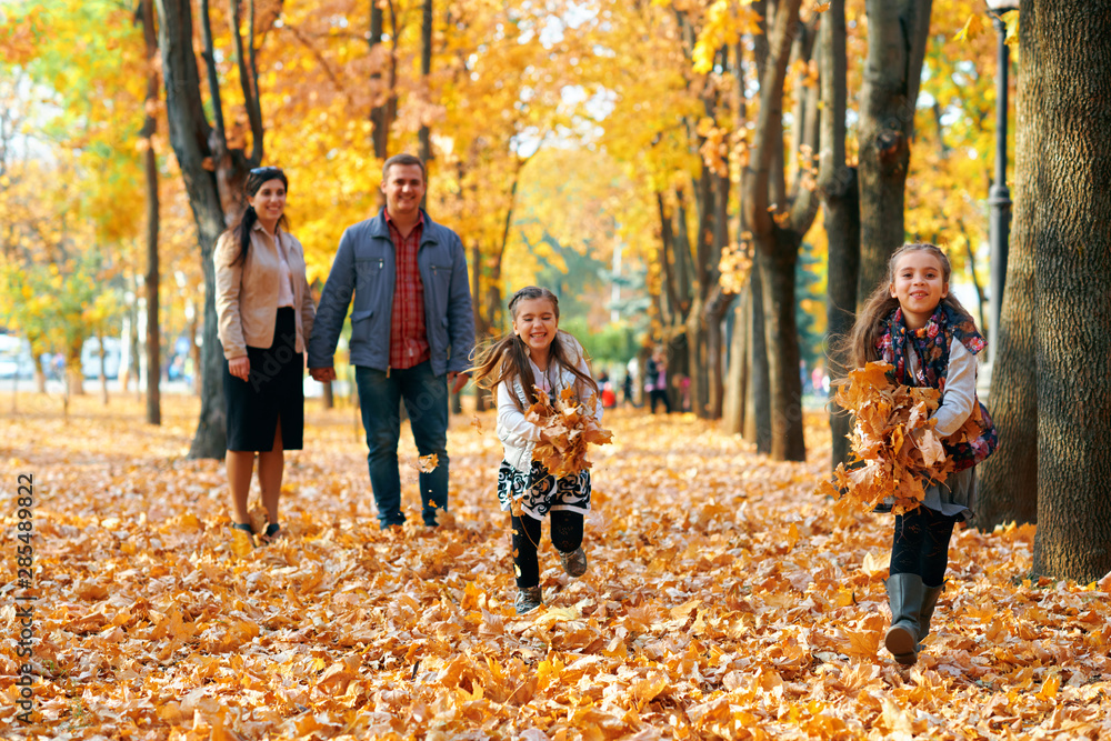 Fototapeta Happy family having holiday in autumn city park. Children and parents posing, smiling, playing and having fun. Bright yellow trees and leaves