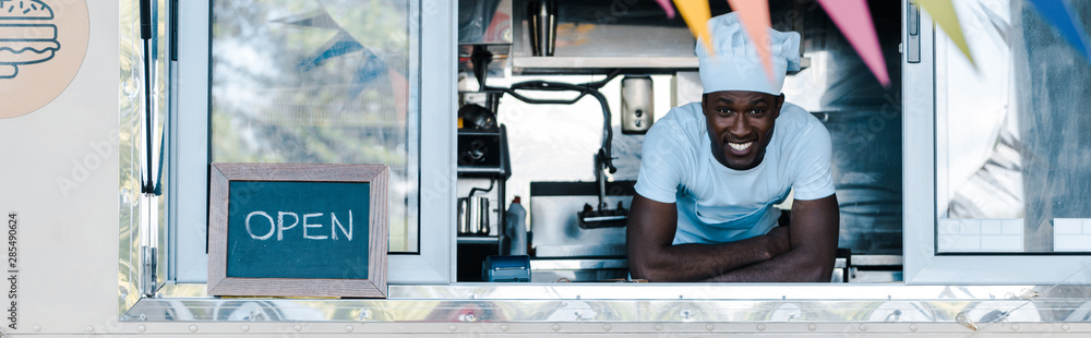 Fototapety, obrazy: panoramic shot of happy african american man in chef uniform smiling from food truck