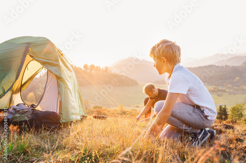 Fototapeta Father and son setting camping tent on the sunset mountain valley at the evening