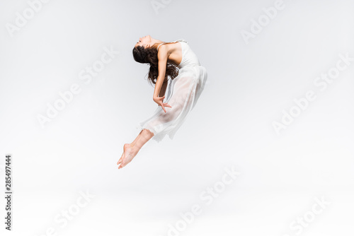 Poster Dance School side view of graceful young ballerina jumping in dance on grey background