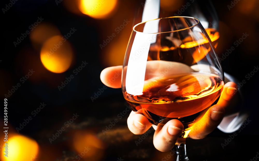 Fototapeta French glowing cognac glass in hand on the dark bar counter background, copy space, selective focus