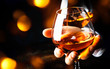 canvas print picture - French glowing cognac glass in hand on the dark bar counter background, copy space, selective focus