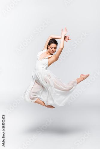 Fotografia beautiful young ballerina dancing in white dress on grey background