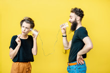 Man And Woman Talking With String Phone Made Of Cups On The Yellow Background. Concept Of Communication