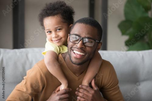 Obraz Head shot portrait of smiling African American father piggyback son - fototapety do salonu