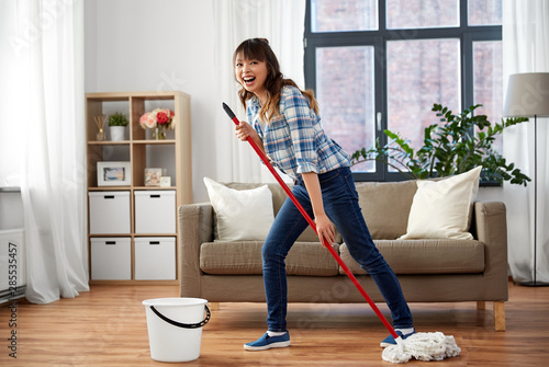 Pinturas sobre lienzo  people, housework and housekeeping concept - happy laughing asian woman with mop