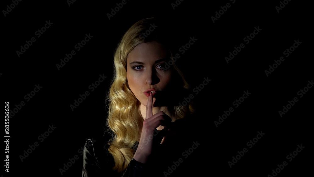 Fototapeta Pretty blond female showing silence gesture against dark background, spying