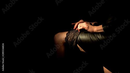 Obraz Female strip dancer wearing stockings, demonstrating leg, temptation concept - fototapety do salonu