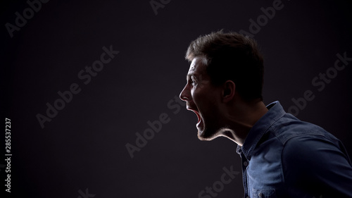 Fotografiet Frustrated man emotionally screaming isolated on black background, life problems