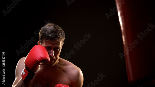 Motivated boxer training with boxing bag, hardly working to be professional Wallpaper Mural