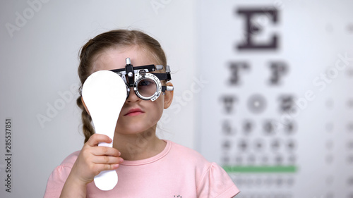Foto auf Gartenposter Lineale Wachstum Child in special glasses with eye closed checking vision, astigmatism diagnosis