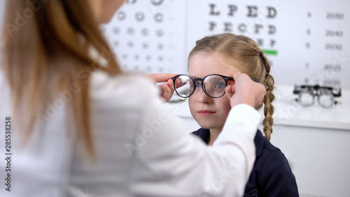 Cuadros en Lienzo Optician putting glasses on schoolgirl, checking vision and recommending glasses