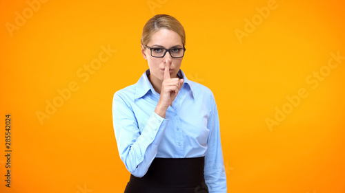 Photo  Young female secretary making silence gesture and winking on camera, secret