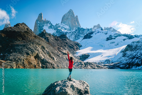 Obraz Tourist woman on Mount Fitzroy, Patagonia trek. Scenic view of snowcapped mountain tops. Blue sky, turquoise blue lake and scenic rock landscape. Shot in Argentina. Nature, travel, adventure, hiking. - fototapety do salonu