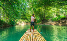 Man Rowing Bamboo Raft, Martha Brae. Tourist Boy Whilst On Cruise  On Vacation In Montego Bay, Jamaica, Caribbean.