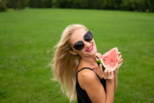 A Pretty Woman Looks On The Field With Photochromic Glasses In Her Hand Holding A Slice Of Watermelon In A Black Hat From Behind A Beautiful Forest.