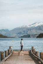 Snow Covered Mountain Near Lake With Man Standing On Deck
