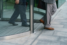 Two Bisnessmen Leave The Office Building. Revolving Door And Men Feet Photography. Urban Office Lifestyles In The End Of Day. Back View.