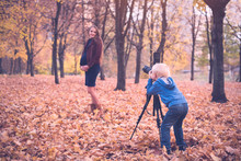 Little Blond Boy With A Large Reflex Camera On A Tripod. Photographs A Pregnant Woman. Family Photo Session