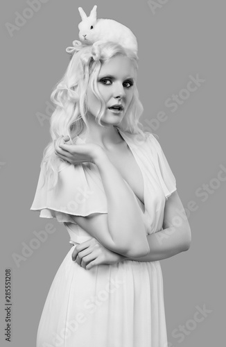 Albino blond girl in elegant dress posing with cute little rabbit Wallpaper Mural