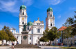 canvas print picture - St. Stephens Basilica is an old white church with green metal domes on top of the towers in Passau, Germany. In front of the Church is a statue of Maximillian Joseph