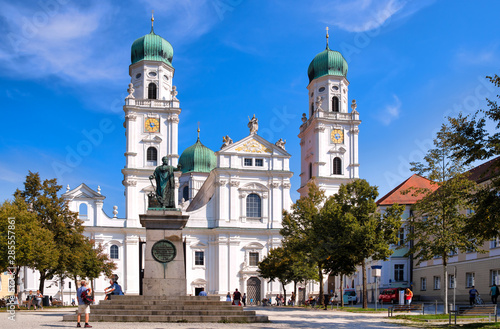 Obraz St. Stephens Basilica is an old white church with green metal domes on top of the towers in Passau, Germany. In front of the Church is a statue of Maximillian Joseph - fototapety do salonu