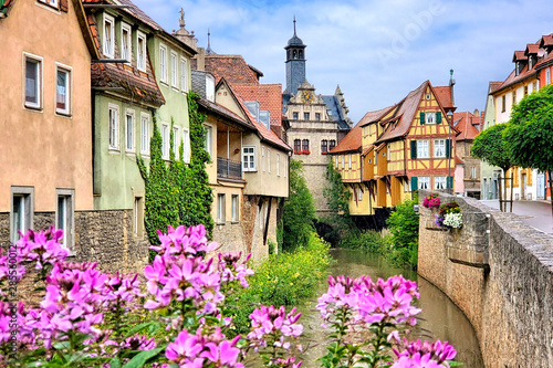 Fotobehang Oude gebouw Picturesque old buildings and flowers lining a canal in the town of Marktbreit, Bavaria, Germany