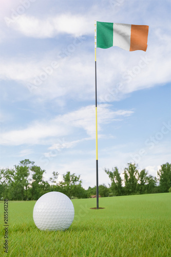 Ireland flag on golf course putting green with a ball near the hole