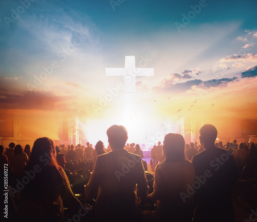 Valokuva Worship concept: Group of people holding hands praying worship at sunset backgro