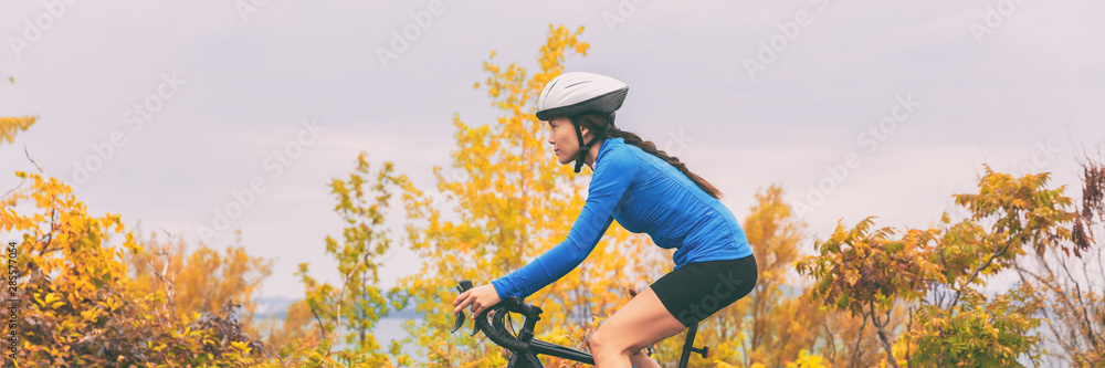 Fototapety, obrazy: Autumn sport active lifestyle cyclist woman doing bicycle in fall nature forest background . Panoramic header landscape.