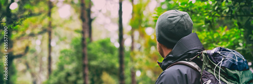 Obraz Hiking hiker man on hike with winter hat and bag in forest background landscape - Panoramic banner. - fototapety do salonu