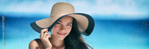 Beach asian woman skin sun protection hat on summer vacation miling tanning banner panorama. Suntan skincare beauty model face portrait panoramic background.