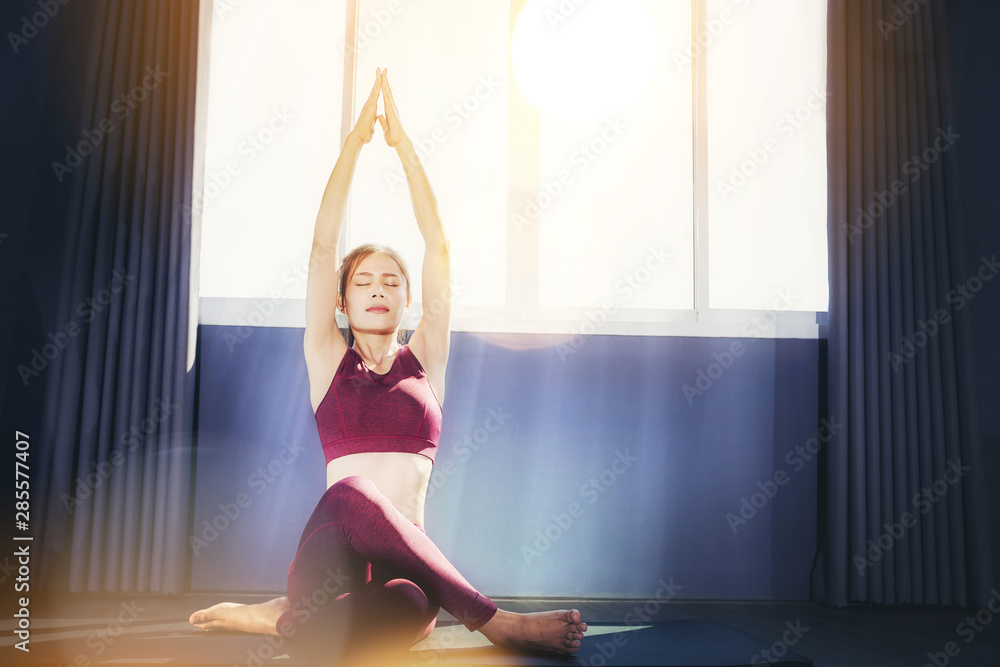 Fototapeta Pretty woman doing yoga pose by sitting at warm light in fitness gym.