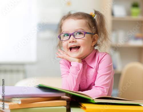 Fotografía Smart kid girl in eye glasses reading books in her room
