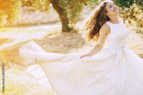 Photo sur Toile Pain Beautiful long-haired bride in a magnificent white dress walking in nature