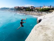 Crazy Tourist Young People On Vacation Play With Ocean Water - Young Teenager Jump Over A High Cliff Doing Trick Back Flip And Having A Lot Of Fun  Enjoying The Summer Holiday Outdoor Leisure Activity
