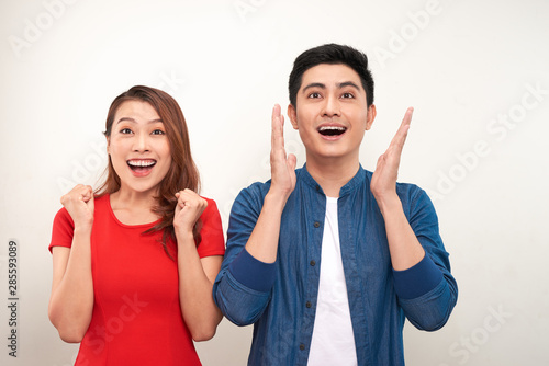 Fotografie, Obraz Young asian couple in love over isolated background celebrating surprised and am
