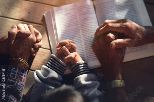 Fototapeta The boy prayed on the table. The family prayed together. obraz