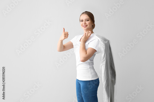 Fototapeta Woman with clothes after dry-cleaning showing thumb-up on light background
