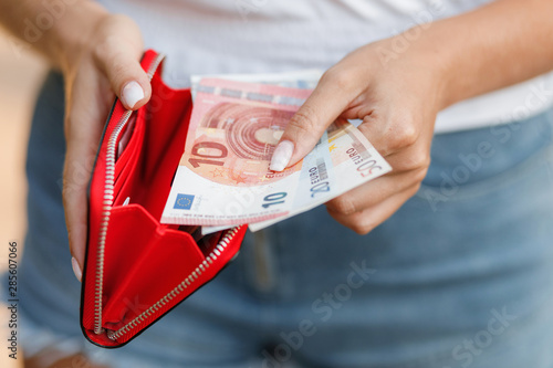 Fotomural  Female hands gets money from the wallet. Euro cash background.