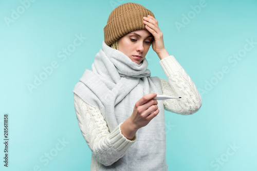 Fotografie, Tablou Young woman having flue taking thermometer against blue background