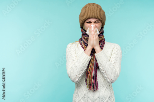 Fotografie, Tablou Health and medicine concept - Young woman blowing nose into tissue, on a blue background